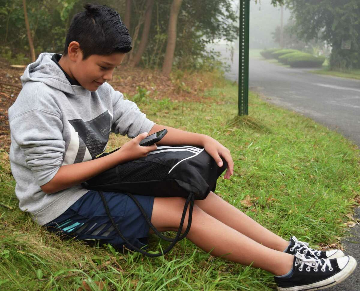 Dylan Nieto checks his phone before hopping on the bus to go to Schaghticoke Middle School for his first year as a sixth grader.