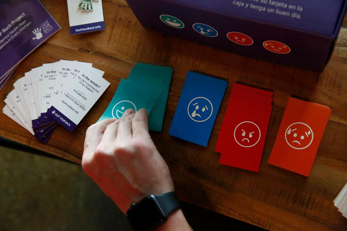 Jason Kirby, Ella general manager, deposits a mood card into a mood box as he checks in at an