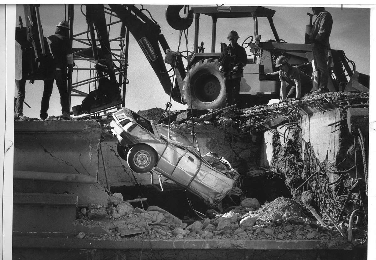 QUAKE/B/30OCT89/MN/STEVE RINGMAN THE CHRONICLE. BUCK HELM'S CAR, A SUZUKI SPRINT, FOUND NEAR 28TH AND PERALTA ON THE 880 CYPRESS STRUCTURE OF THE NIMITZ FREEWAY IN OAKLAND. Car was damaged when the Cypress Freeway collapsed on top of the lower deck during the 7.1 1989 Loma Prieta earthquake. Photo by Steve Ringman