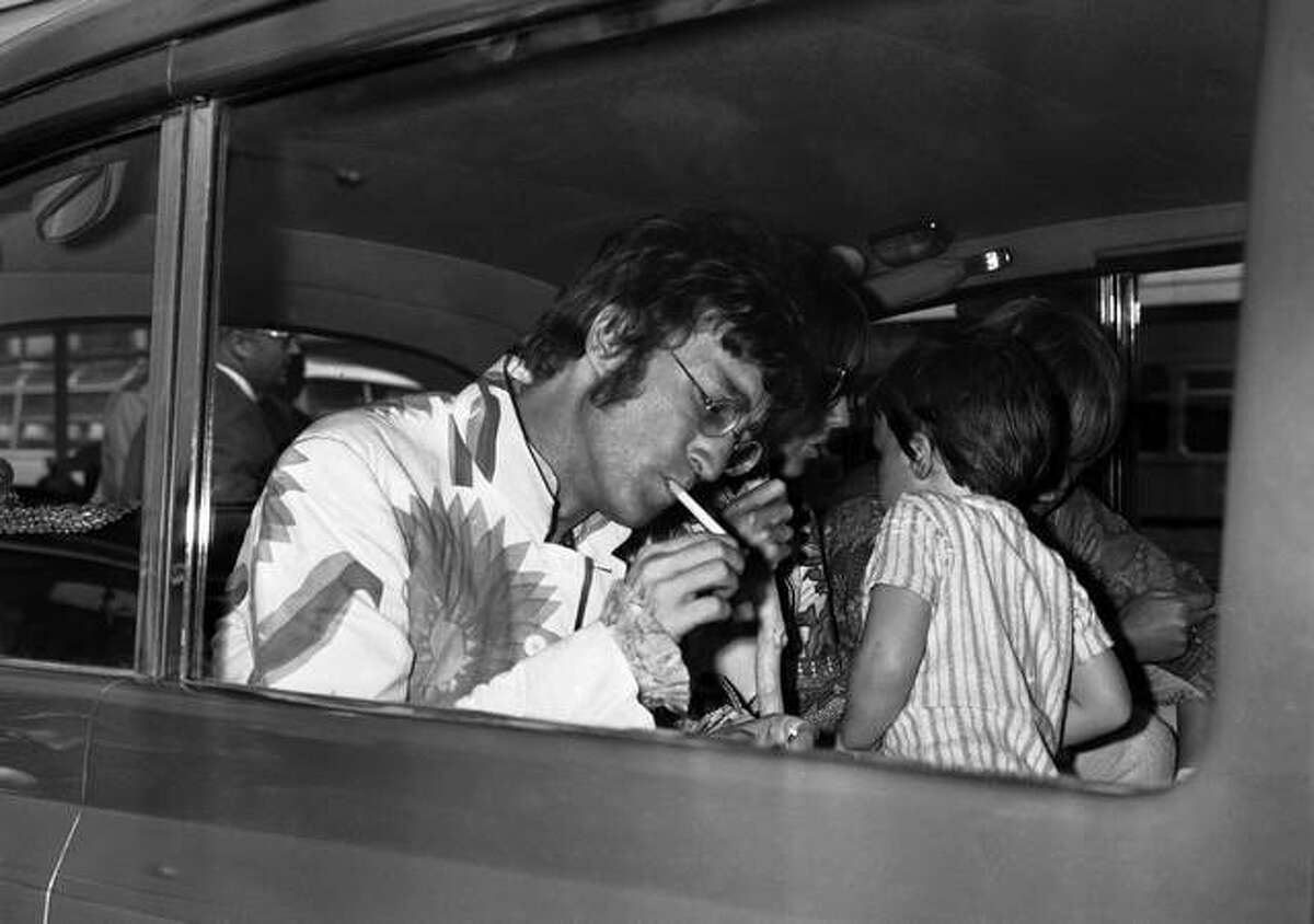 John Lennon from The Beatles lights a cigarette on his arrival at Heathrow Airport in London from Athens on July 31, 1967, with his then-4-year-old son Julian. (Victor Boyton/Associated Press)