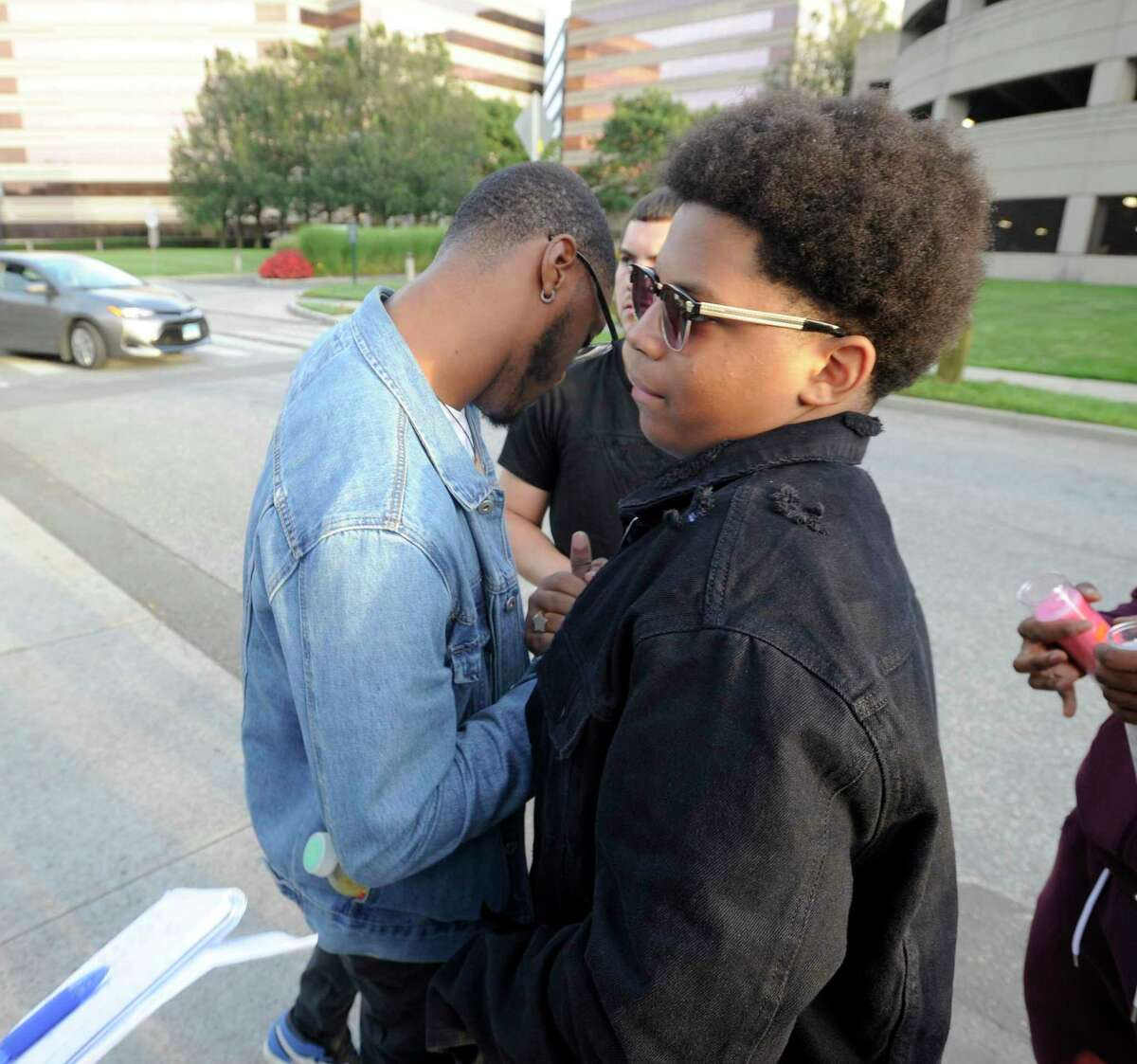 Kyaire Johnson is greeted by Talik Burgess on Tuesday August 27, 2019 at the scene where Johnson brother Ky-Mani Pollack and NiShawn Tolliver were fatally killed in a car crash early Monday morning. Four other individuals were injured in the crash at Canal and Ludlow streets.