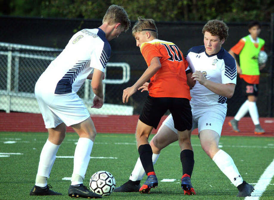 Father McGivney's Jonah Mitan, left, and Thomas Hyten, right, battle for the ball with a Mount Vernon player during Tuesday's Metro Cup game at Belleville Althoff. Photo: Scott Marion/The Intelligencer