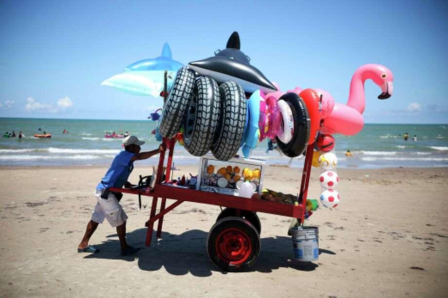 Un vendedor empuja su carro equipado con llantas inflables y vasos de futas en la orilla de Playa Bagdad cerca de la frontera con Matamoros, México. Photo: Emilio Espejel /Associated Press / Copyright 2019 The Associated Press. All rights reserved