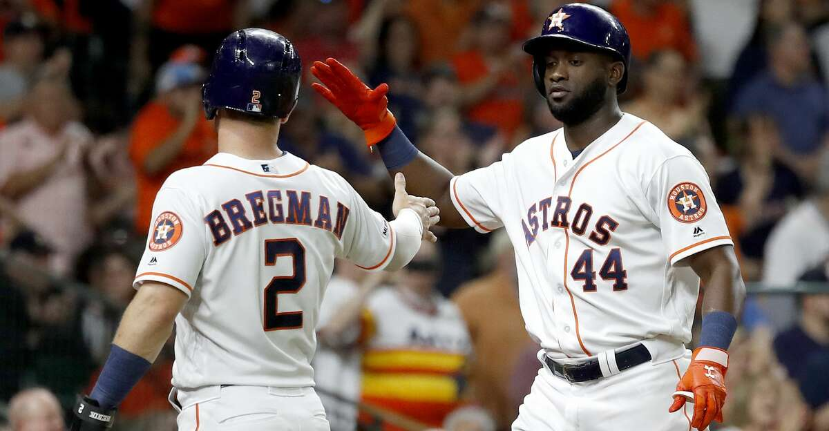 Houston Astros Yordan Alvarez (44) and Alex Bregman (2) celebrate their runs scored on Yuli Gurriel's double during the fourth inning of an MLB baseball game at Minute Maid Park, Tuesday, August 27, 2019.