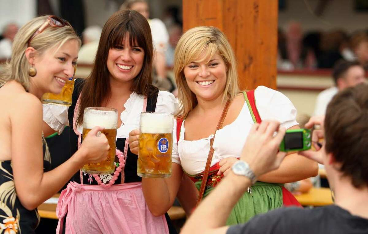 MUNICH, GERMANY - SEPTEMBER 21: Three women pose for a picture at the Hofbraeuhaus beer tent on September 21 2009 in Munich, Germany. Oktoberfest is Germany's and the world largest fair. About six million people attend the sixteen-day festival during late September and early October. (Photo by Miguel Villagran/Getty Images)