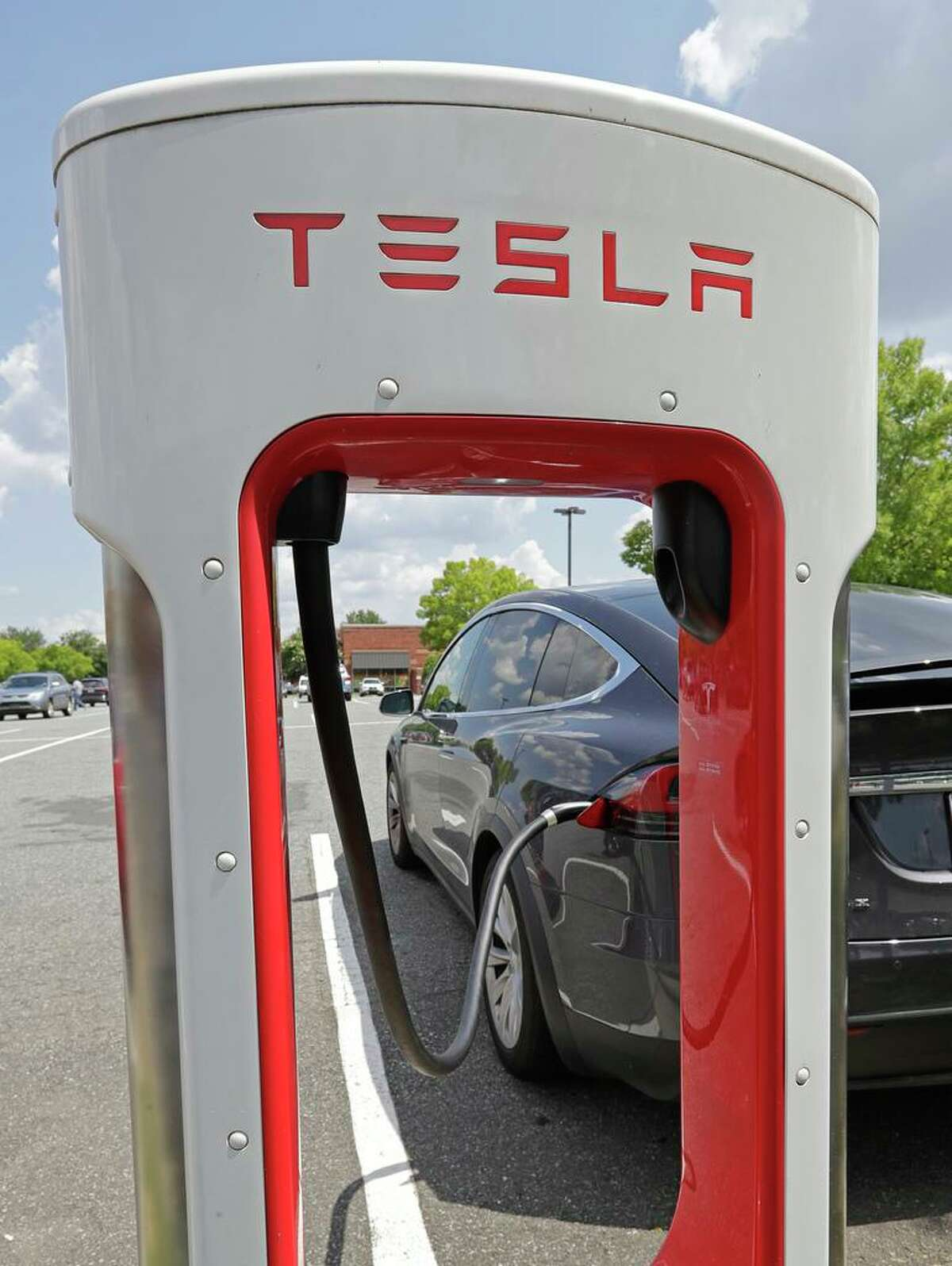 A Tesla vehicle is shown charging at a Tesla Supercharger site in Charlotte, N.C., Friday, July 19, 2019. (AP Photo/Chuck Burton)