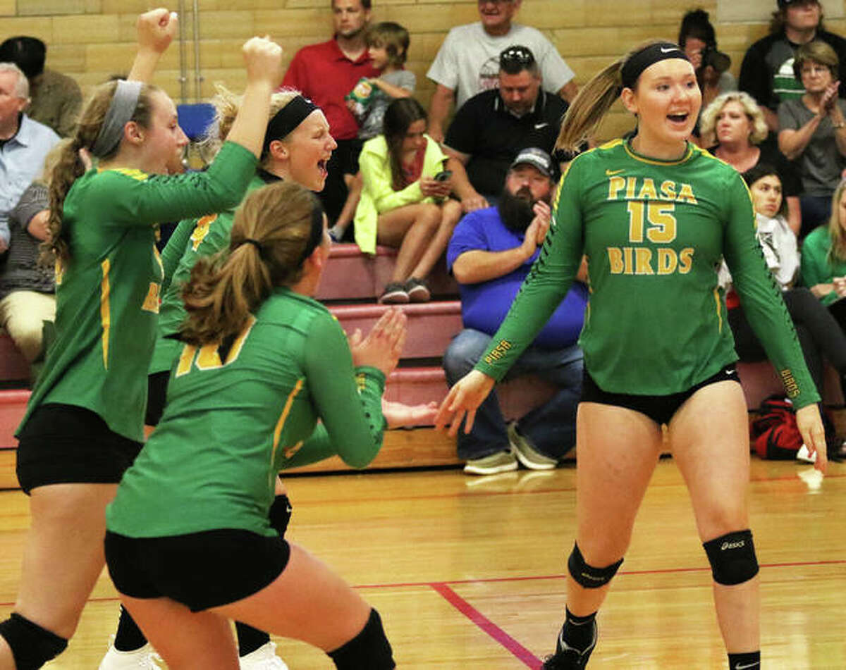 Southwestern's Bailey Nixon (right) celebrates a point with teammates during a three-set win over Granite City on Tuesday night at the Roxana Tournament. The Birds went 3-0 to win their pool.