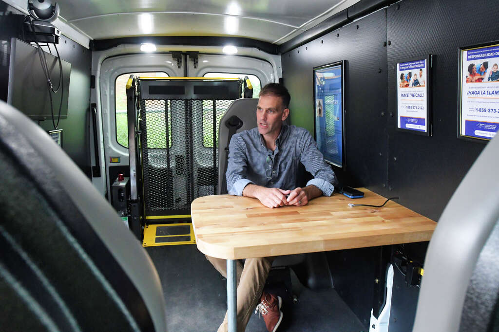 Chad Putman, project director of the Center for Treatment Innovation Project at New Choices Recovery Center, sits in the mobile treatment van on Tuesday, Aug. 27, 2019, in Schenectady, N.Y.    (Paul