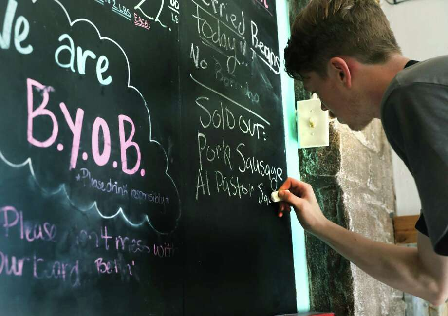 Dusty Dworak, pit hand and slicer at 2M Smokehouse, writes down what's sold out on a note board near the entrance. The barbecue at 2M Smokehouse is often sold out due to its popularity and limited amounts. Photo: Bob Owen / ©2019 San Antonio Express-News
