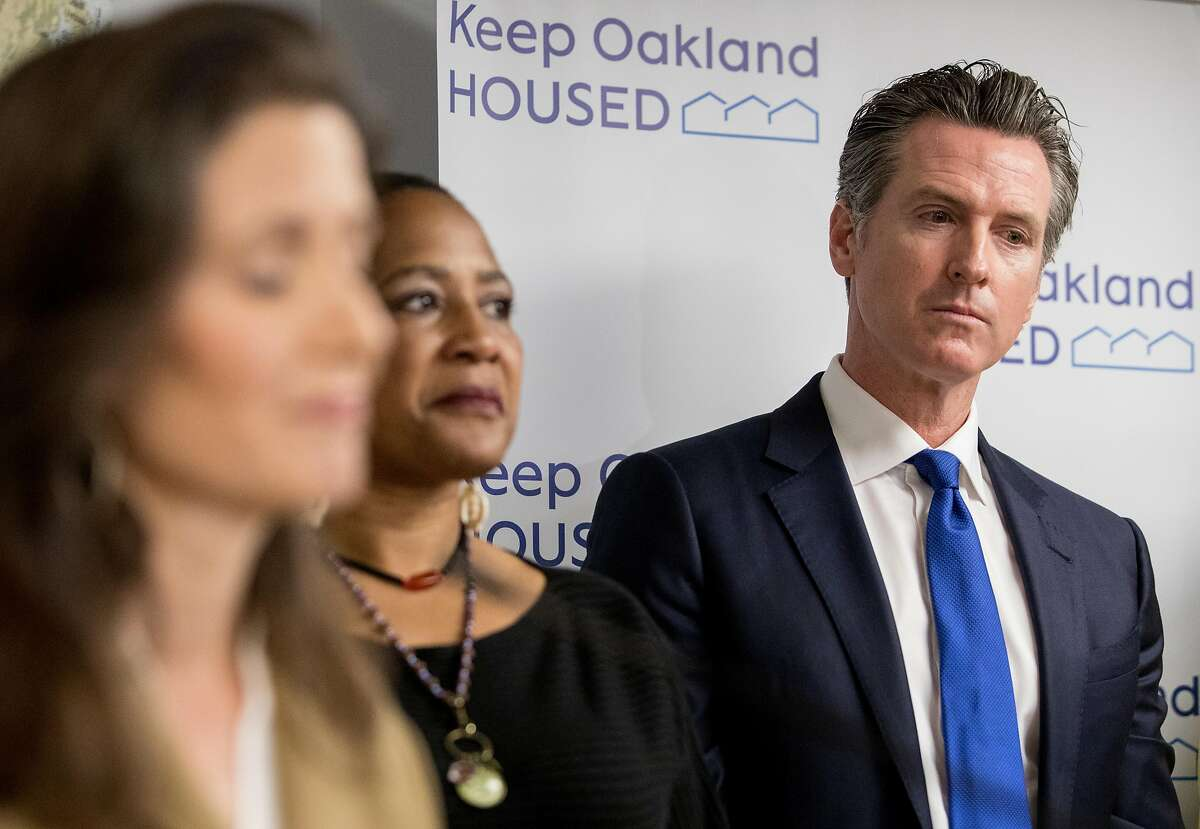 California Governor Gavin Newsom listens during Oakland Mayor Libby Schaaf's speech before announcing a newly created state-level homeless commission while standing alongside Alameda County and state officials during a press conference at the Henry Robinson Multi-Service Center in Oakland, Calif. Tuesday, May 21, 2019.