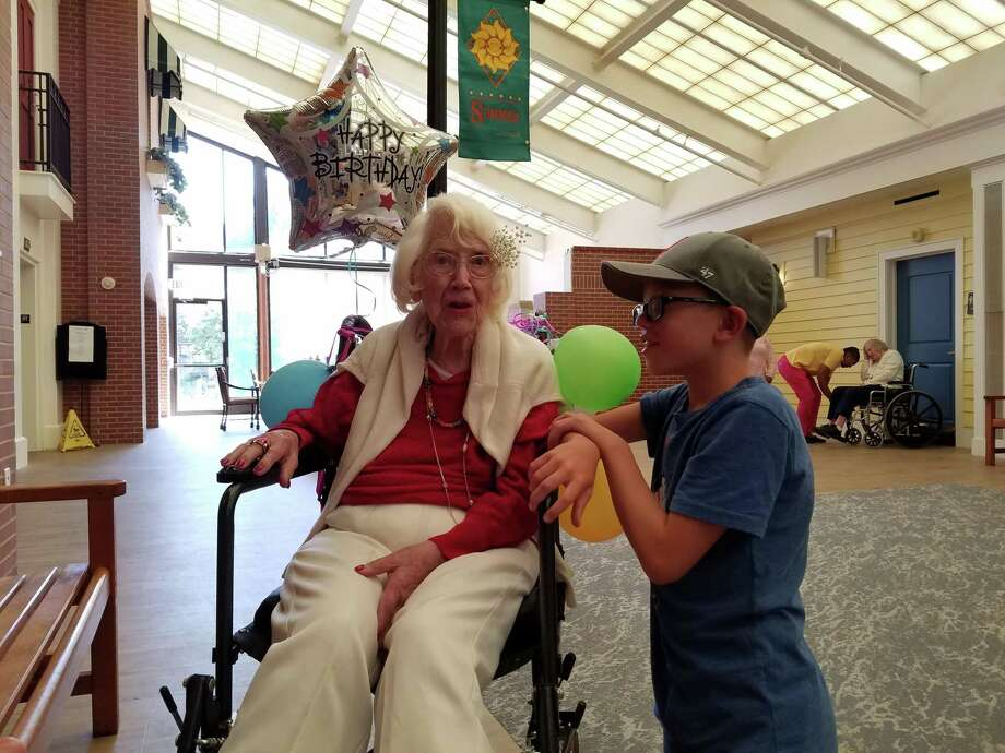 Camille Hyman celebrates her birthday with family members at the Waveny LifeCare Network in New Canaan on Aug. 27, 2019, as her great-grandson Jack Spillane stands beside her. Photo: Grace Duffield / Hearst Connecticut Media