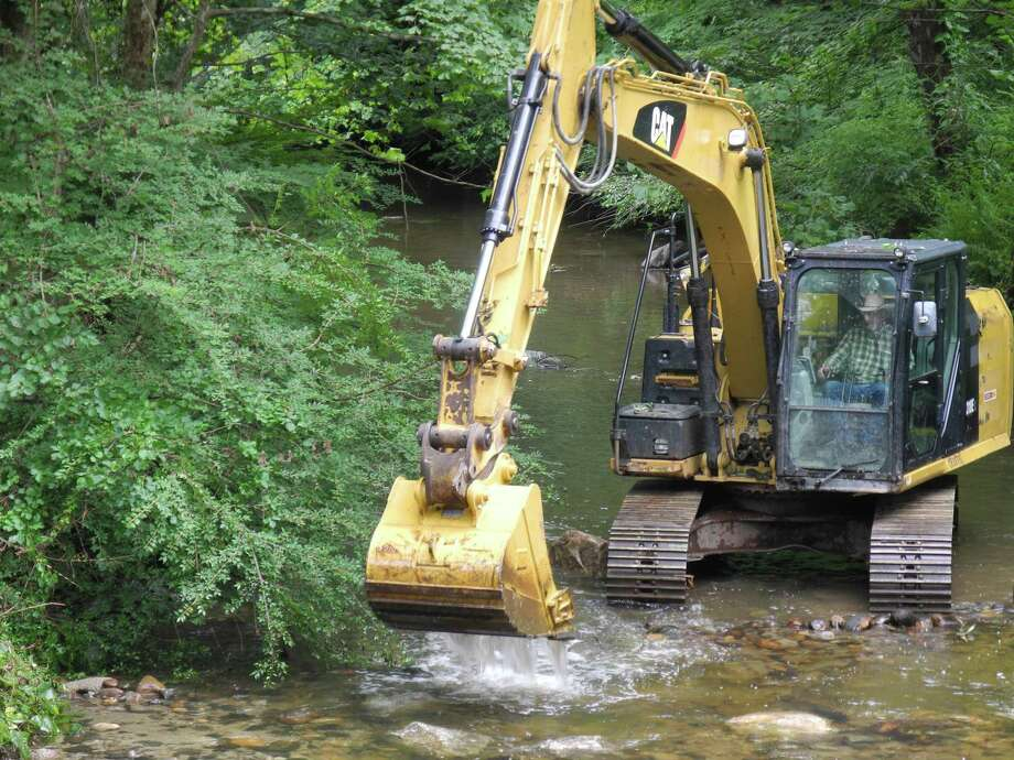 Ron Weekes of Trout Scapes River Restoration guides a track excavator to create deep pools for fish in the Norwalk River at Schenck's Island, Wilton, Conn., on Aug. 23, 2019. Photo: Jeannette Ross / Hearst Connecticut Media / Wilton Bulletin