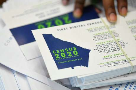 FILE - In this Aug. 13, 2019, file photo a worker gets ready to pass out instructions in how fill out the 2020 census during a town hall meeting in Lithonia, Ga. Foreign-born residents had higher rates of being employed than those born in the United States last year, and naturalized immigrants were more likely to have advanced degrees than the native-born, according to figures released Monday, Aug. 19, by the U.S. Census Bureau. (AP Photo/John Amis, File)