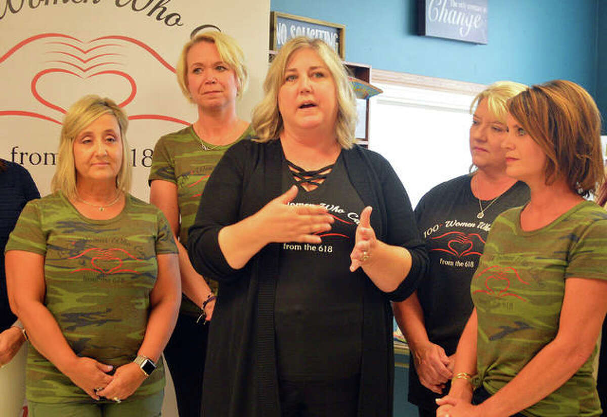 Main Street Community center director Sara Birkbigler, middle, talks during a ceremony on Tuesday, when Main Street received a check for $31,650 from 100+ Plus Women Who Care from the 618.