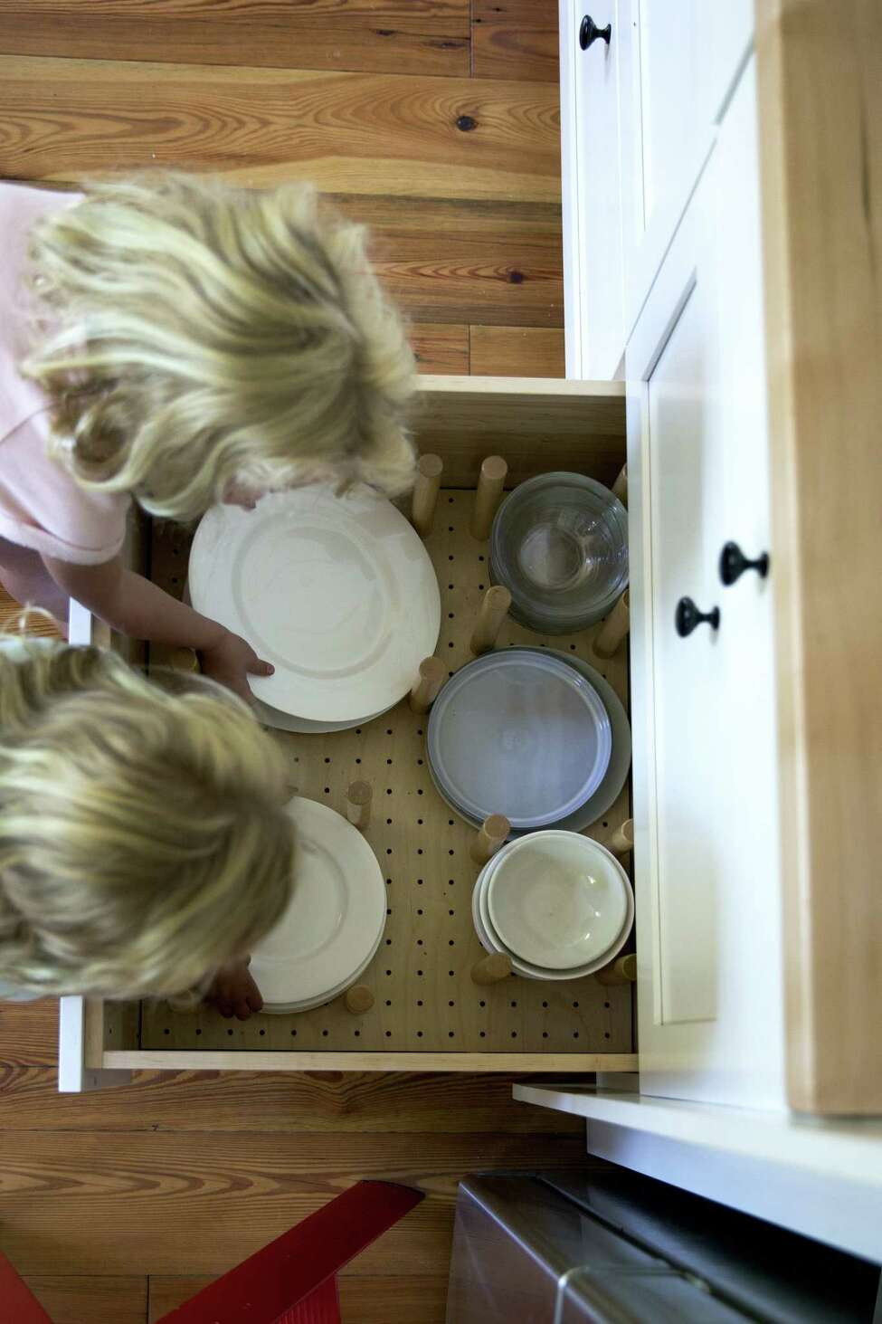 When designing her new kitchen, food blogger Ali Stafford wanted dishes and glasses stored at a height her children could reach them. Peg inserts keep the dishes neat and secure. (Photo by Ali Stafford)