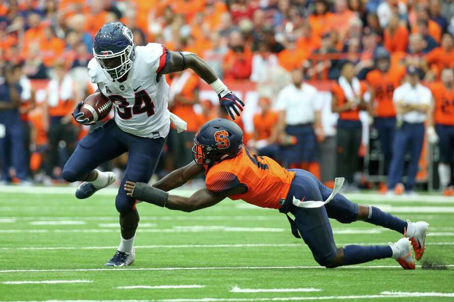 UConn running back Kevin Mensah runs with the ball as Antwan Cordy of Syracuse makes a diving tackle last season. Photo: Rich Barnes / Getty Images / 2018 Getty Images