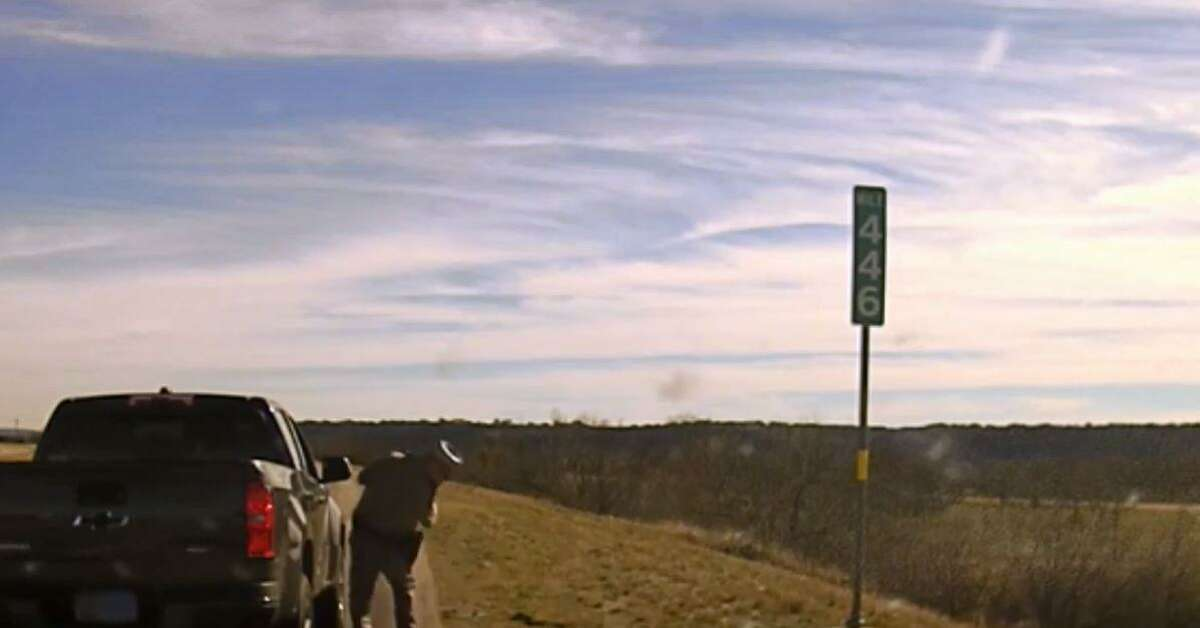 Trooper Lee Meadow ducks as a shot is fired out of a pickup he'd just stopped for a traffic violation.