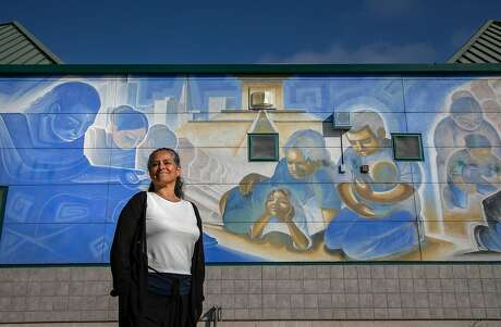Claudia Mel�ndez Salinas poses for a portrait in front of a mural by Salinas artist Jose Ortiz at Alisal Community School on Wednesday, August 21, 2019 in Salinas, Calif.