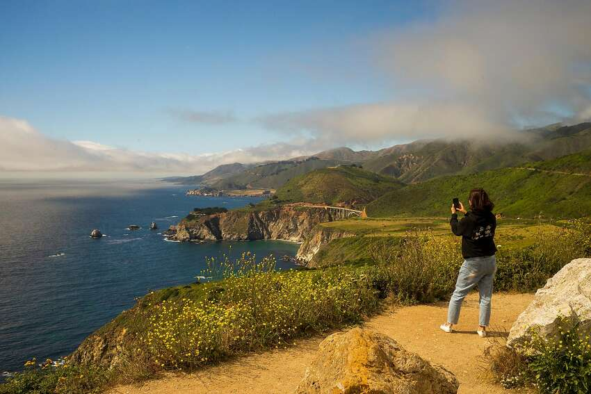A woman takes a photo of the oft-shot Bixby Bridge from atop Hurricane Point in Big Sur that offers a sweeping panorama of the Pacific.