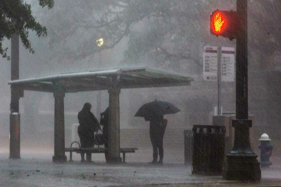 Communters take shelter under a bus stop on Congress as heavy rains pours on downtown on Wednesday, Aug. 28, 2019, in Houston. Photo: Brett Coomer, Staff Photographer / © 2019 Houston Chronicle