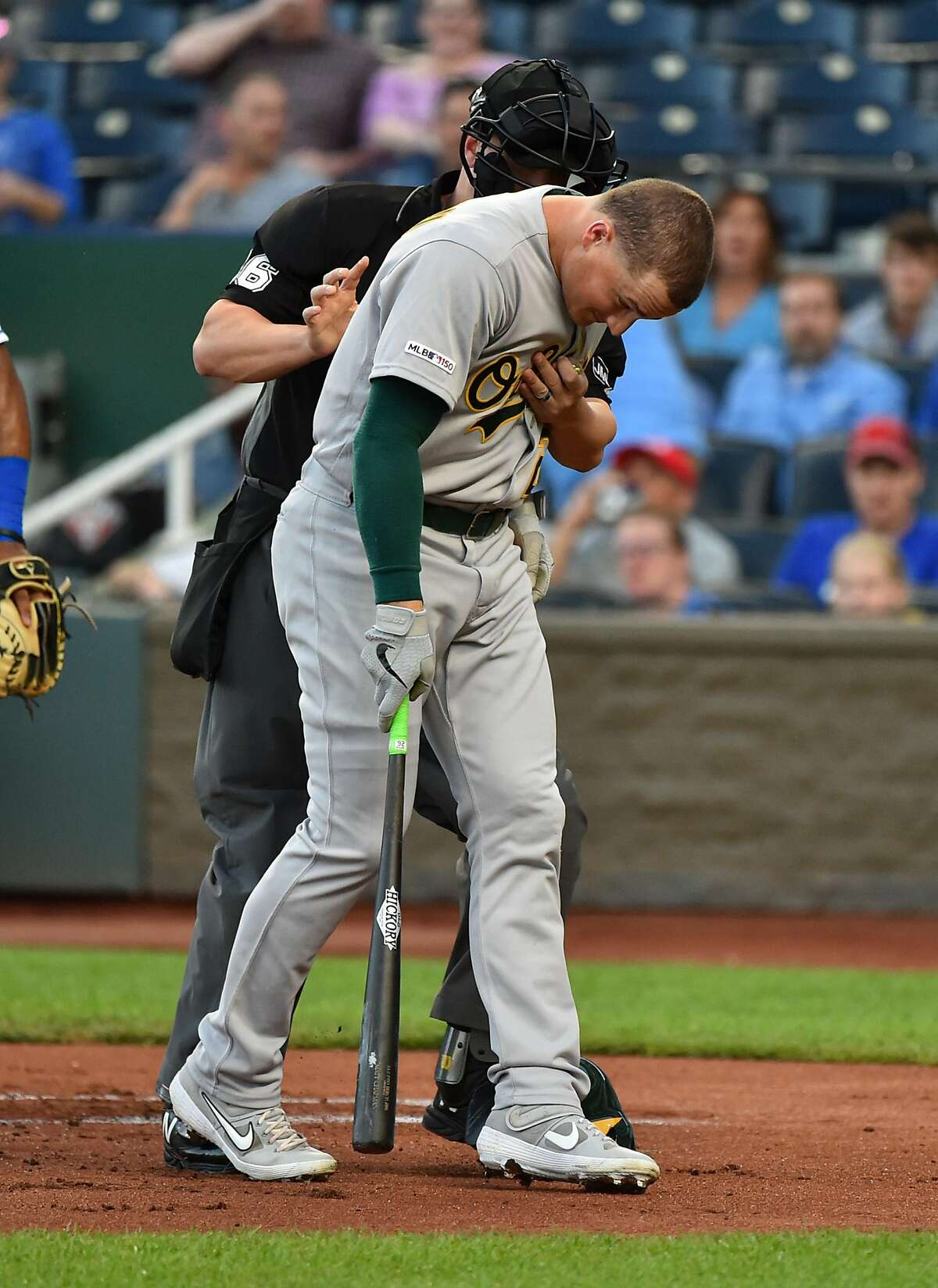 KANSAS CITY, MISSOURI - AUGUST 28: Matt Chapman #26 of the Oakland Athletics is helped by plate umpire Chris Segal after he was struck by a pitch thrown by starting pitcher Jakob Junis #65 of the Kansas City Royals in the first inning at Kauffman Stadium on August 28, 2019 in Kansas City, Missouri. (Photo by Ed Zurga/Getty Images)