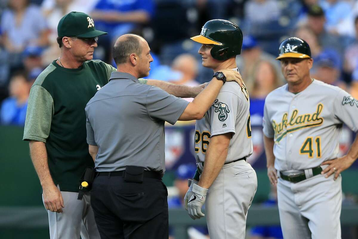 Oakland Athletics manager Bob Melvin, left, and a trainer check on Matt Chapman (26) after he was hit by a pitch during the first inning of the team's baseball game against the Kansas City Royals at Kauffman Stadium in Kansas City, Mo., Wednesday, Aug. 28, 2019. (AP Photo/Orlin Wagner)