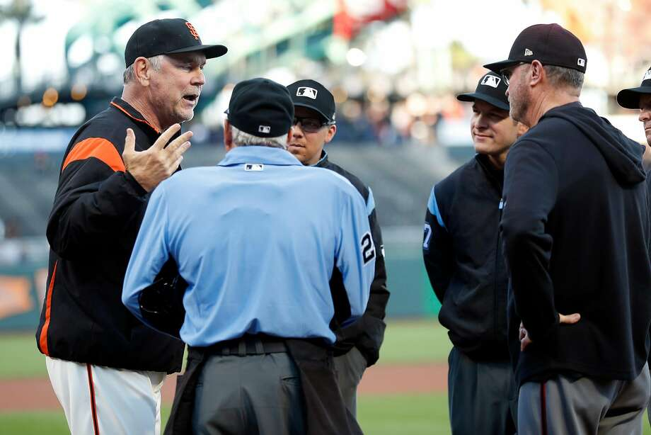 Giants manager Bruce Bochy chats with umpires after presenting the lineup card before facing the Arizona Diamondbacks at Oracle Park on Tuesday. Photo: Scott Strazzante / The Chronicle