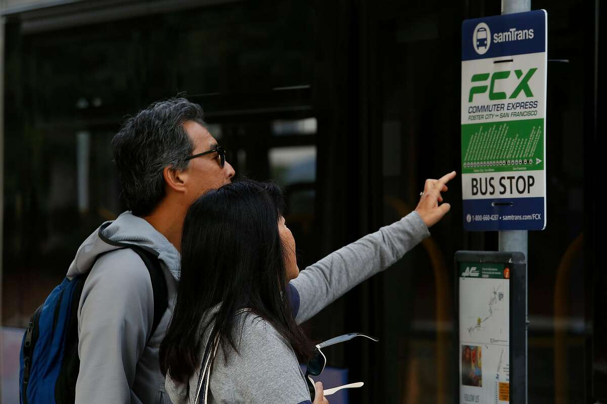 Michael (l to r) and Linda Hirabayashi of Foster City look at the information on a sign for the SamTrans' Foster City Commuter Express bus as they wait at a bus stop on Wednesday, August, 28, 2019 in Foster City, CA.