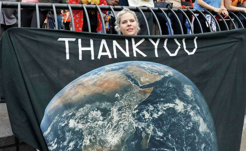 Jemila MacEwan, a supporter of Swedish environmental activist Greta Thunberg, awaits her arrival at a marina in New York, Wednesday, Aug. 28, 2019. Thunberg is scheduled to address the United Nations Climate Action Summit on September 23. (AP Photo/Mark Lennihan)