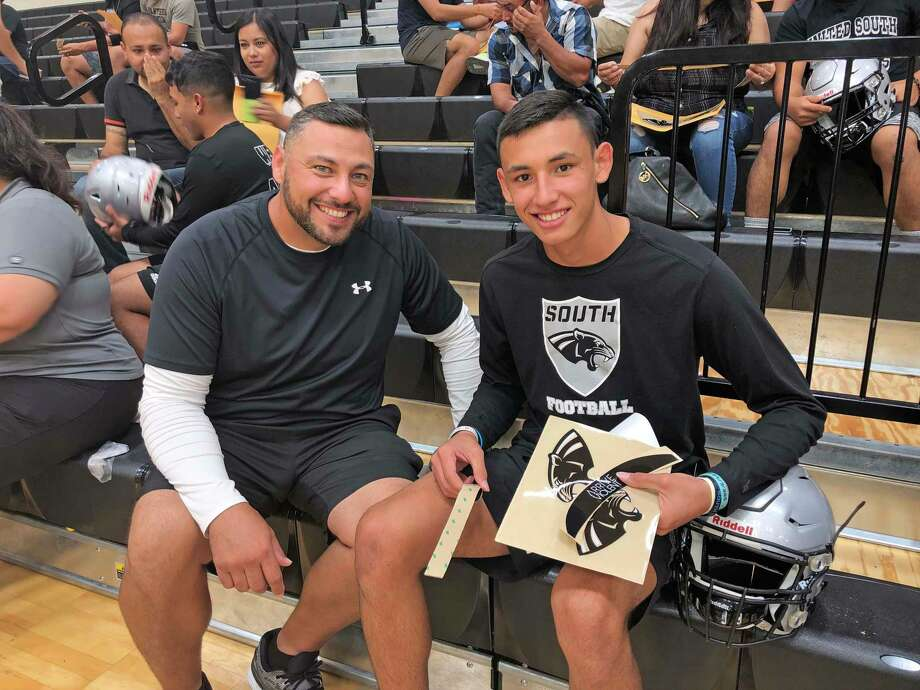 John Leal has coached his son, Johnny in elementary and middle school. They both participated in the 2nd annual Decal with Dads-Loved Ones Wednesday night. Photo: Clara Sandoval /Laredo Morning Times