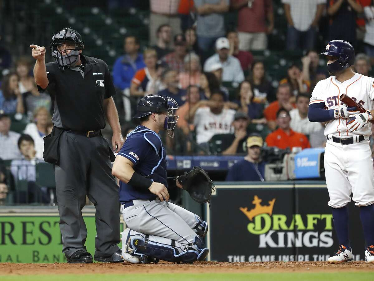 Home plate umpire Greg Gibson (53) warns someone in the Houston Astros dugout chirping about balls and strikes as Jose Altuve (27) batted during the eighth inning of an MLB baseball game at Minute Maid Park, Wednesday, August 28, 2019.