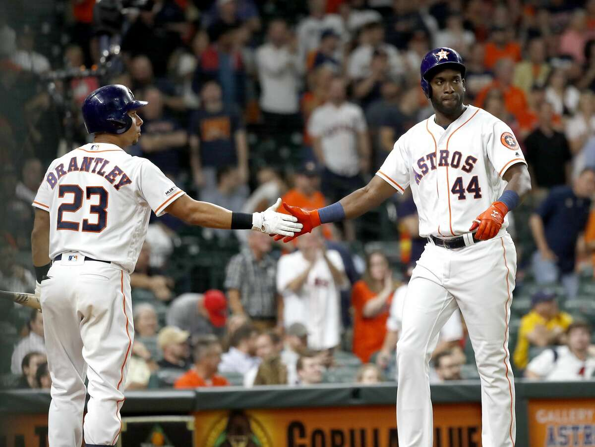 Houston Astros Yordan Alvarez (44) celebrates with Michael Brantley (23) after he scored a run on George Springer's walk during the eighth inning of an MLB baseball game at Minute Maid Park, Wednesday, August 28, 2019.