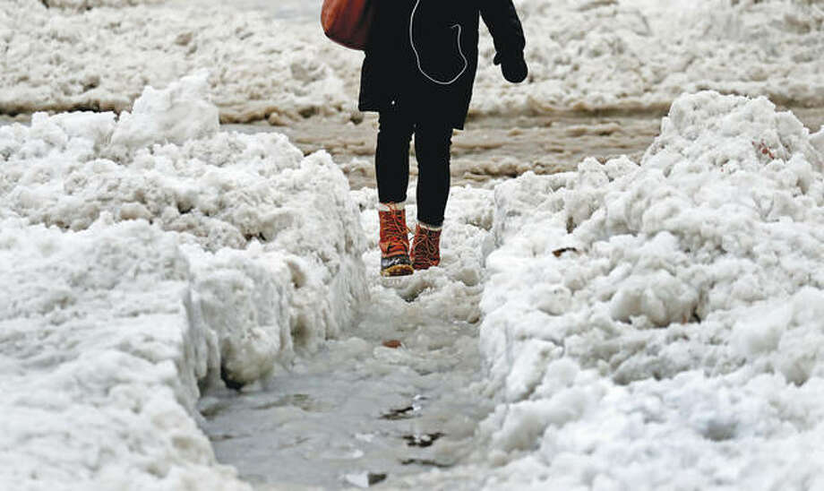 A woman walks a small icy path cut through the snow to cross the street after a winter storm. Photo: David L. Ryan | Getty Images