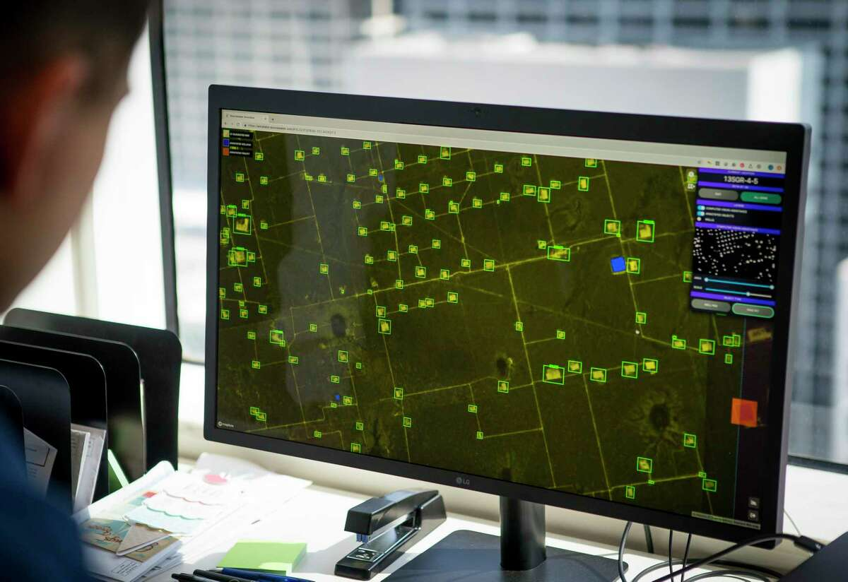 Senior full stack engineer Victor Belous looks at satellite imagery of well pad sites at the company's office in downtown Houston, Tuesday, Aug. 13, 2019.The Houston-based company has developed software and artificial intelligence technology that uses satellite images to track oil field activity in the Permian Basin of West Texas and southeastern New Mexico. Service company uses information learned from the images to land sales contracts while exploration and production companies use them to monitor competitors. With several companies now providing similar services, satellite images have become an increasingly popular tool within the oil & gas industry.