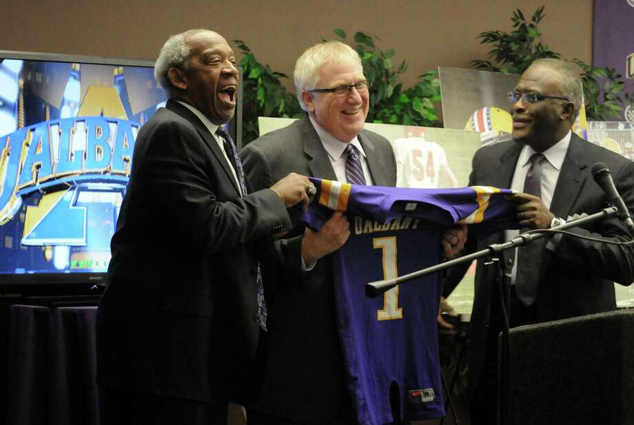 Greg Gattuso, center, new UAlbany football head coach is presented with a team jersey by Athletic Director Lee A. McElroy, left, and University president Robert J. Jones during a press conference to announce his hiring on Dec. 10, 2013, in Albany. (Michael P. Farrell/Times Union) / 00024963A