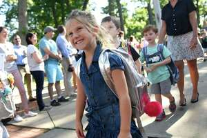 Incoming kindergartener Geena Elezaj smiles while walking with new classmates in the Parade of Learners on the first day of school at Riverside School in the Riverside section of Greenwich, Conn. Thursday, Aug. 29, 2019.