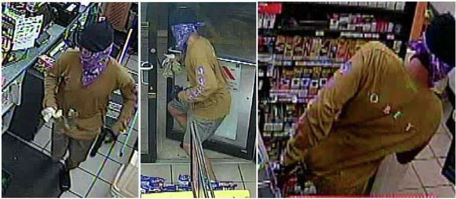 A man with a bandanna concealing his face is seen in a surveillance video still allegedly robbing a gas station in Conroe. Photo: Courtesy Of The Montgomery County Sheriff's Office