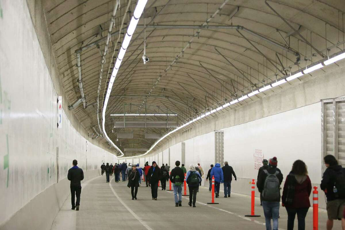 People walk through the new SR 99 tunnel after an offical ribbon cutting ceremony to celebrate its opening, Saturday, Jan. 2, 2019. As many as 100,000 people are expected to attend the weekend-long celebration to say goodbye to the Alaskan Way Viaduct and hello to the new tunnel. (Genna Martin, SeattlePI)