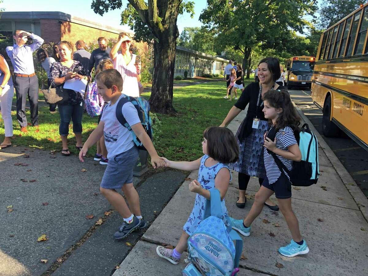 A caring brother stayed close to his younger sister as they got off the bus at Riverfield.