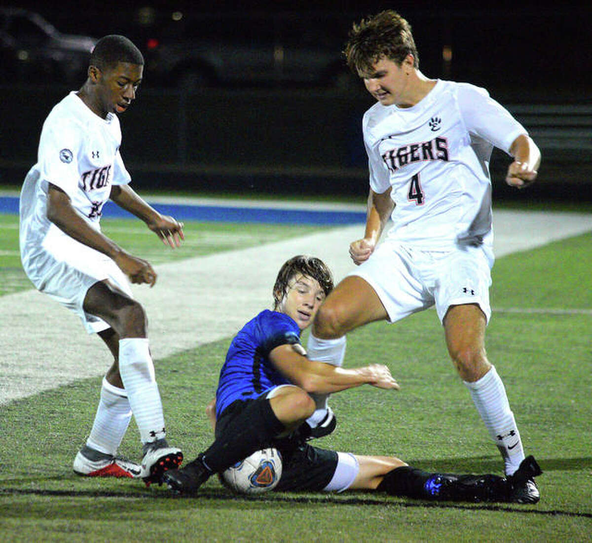 Edwardsville's Chris Agwuedu, left, and Parker Mathews, right, battle for the ball with a Columbia player during Wednesday's Metro Cup game at Columbia.