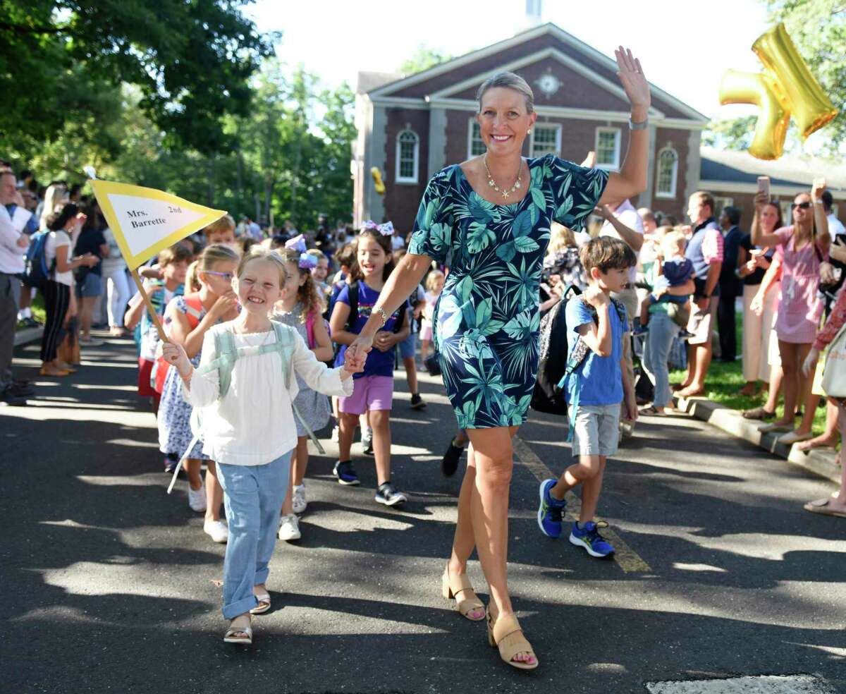 Second-grader Clara Keith walks with her teacher Mrs. Barrette in the Parade of Learners on the first day of school at Riverside School in the Riverside section of Greenwich, Conn. Thursday, Aug. 29, 2019.