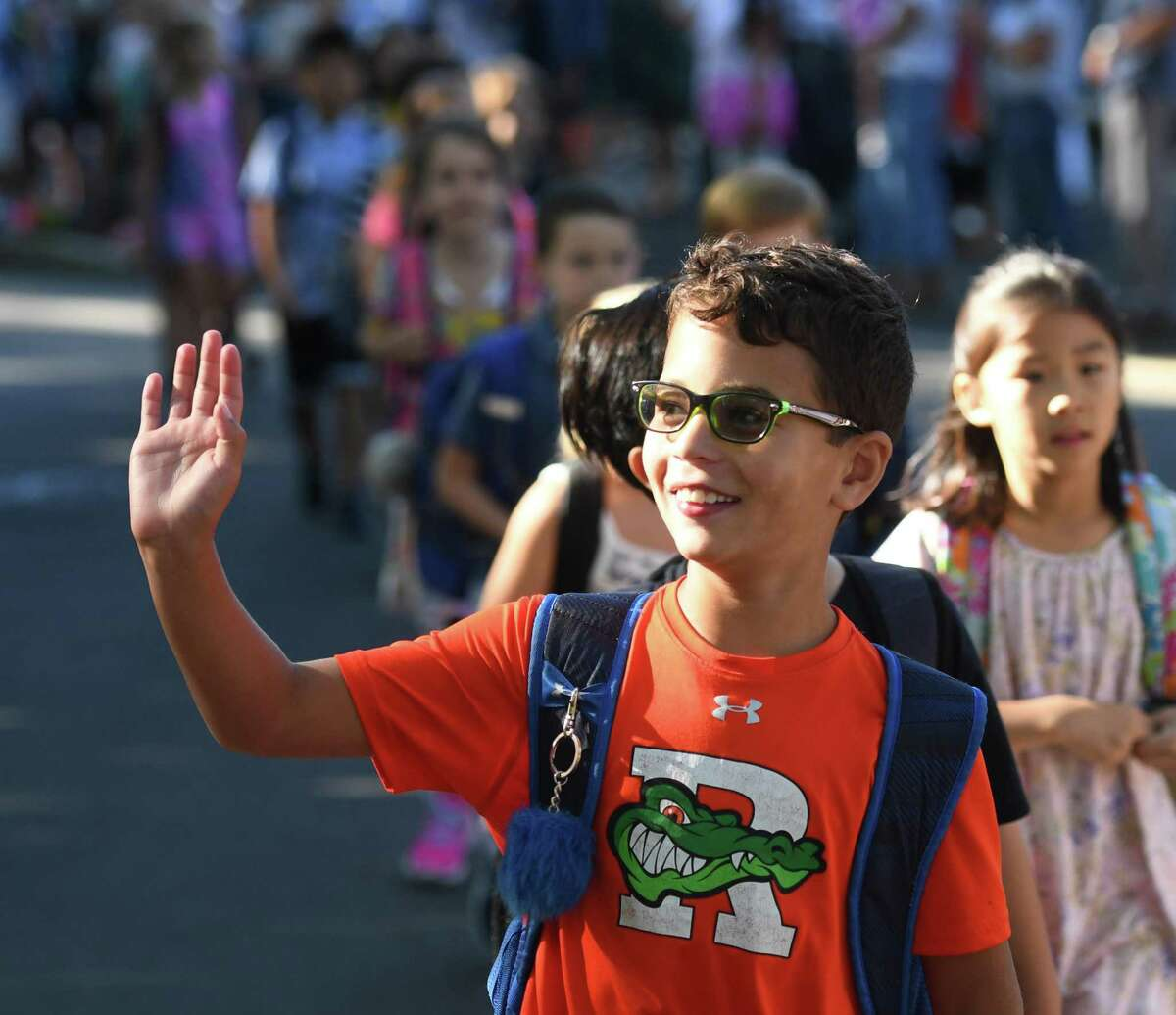 Third-grader Nash Goodman waves to parents in the crowd while walking with his new classmates in the Parade of Learners on the first day of school at Riverside School in the Riverside section of Greenwich, Conn. Thursday, Aug. 29, 2019.