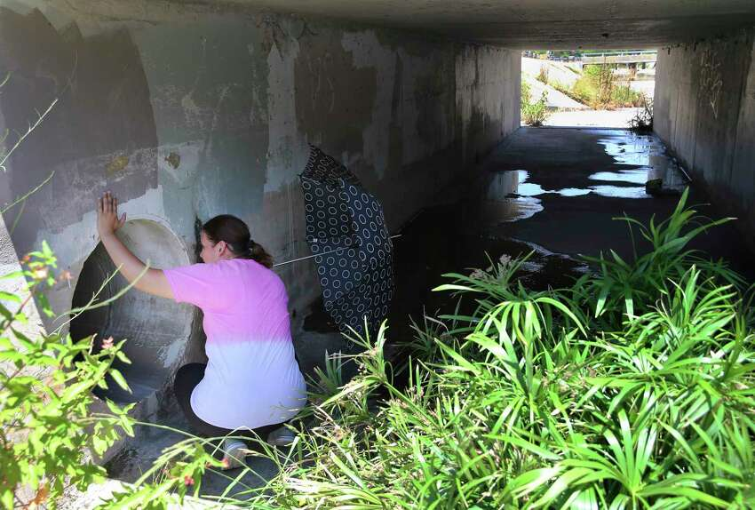 Mireya Lopez of Houston, who is the sister of Cecilia Huerta Gallegos, searches for clues in a drainage culvert as she joins Search & Support San Antonio to look for Gallegos on July 27, 2019. Gallegos, 30, is the mother of four children.