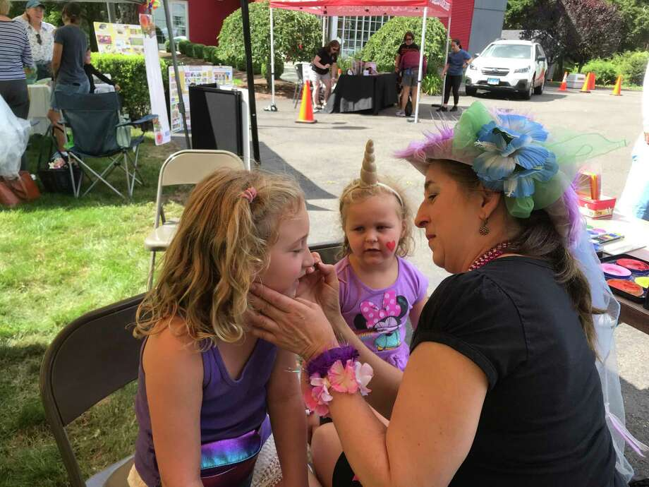 Goldie, 4, watches her sister, Alexa, 8, get her face painted at the Cannon Grange's 87th annual agricultural fair and exposition on Sunday, Aug. 25. The sisters live in Westport. Photo: Susan Shultz /Hearst Connecticut Media