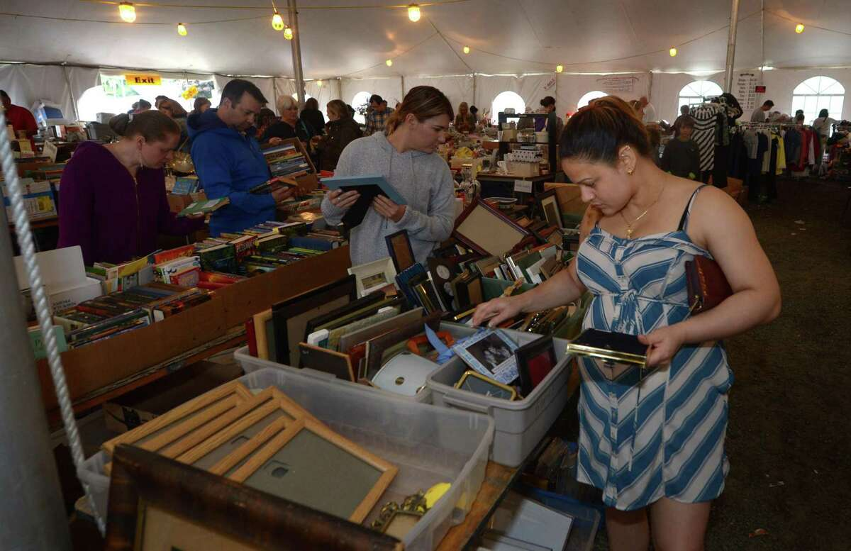 Shopper look through picture frames at last fall's Minks to Sinks sale. In-home consignments begin in September for the sale in October. The sale will benefit the Family and Children's Agency in Norwalk.