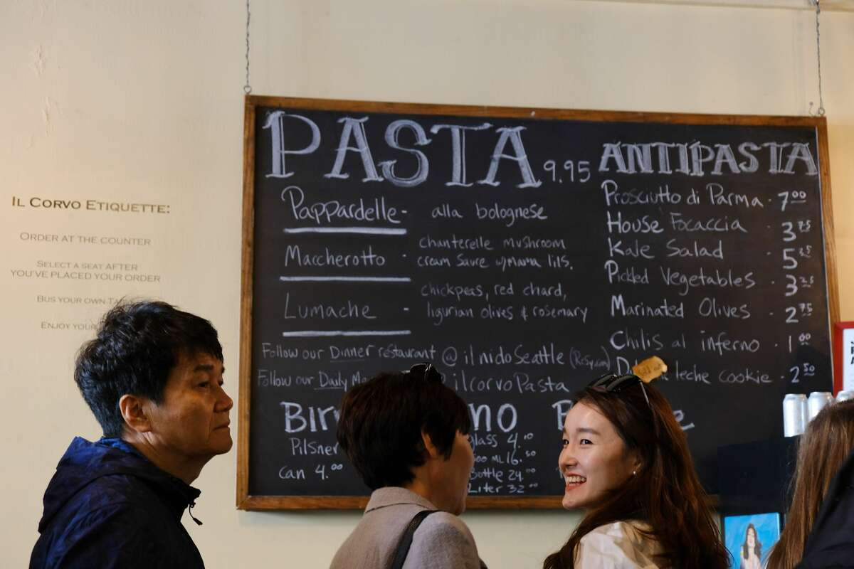 The menu shows the pastas of the day at Il Corvo Pasta as the line to order winds out the door and down the block. The weekday lunchtime line took about 35 minutes of wait time. (Genna Martin, Seattlepi.com)