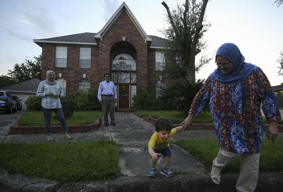 Barbara Zaidan, right, holds her grandson's hand as he jumps outside her home. Photo: Godofredo A. Vásquez/Staff Photographer