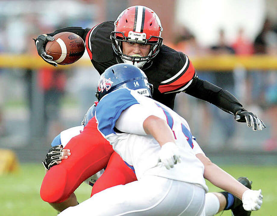 Gillespie's Frank Barrett (back) is pulled down just before making contact with Carlinville's Nick Walton during a SCC game in Gillespie last season. Barrett will move from running back to quarterback in 2019. Photo: James B. Ritter / Telegraph File Photo