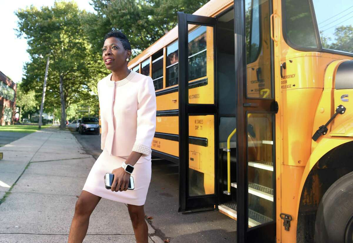Superintendent of School Carol Birks exits a school bus to greet students for the first day of school at Lincoln Bassett Community School in New Haven on August 29, 2019.