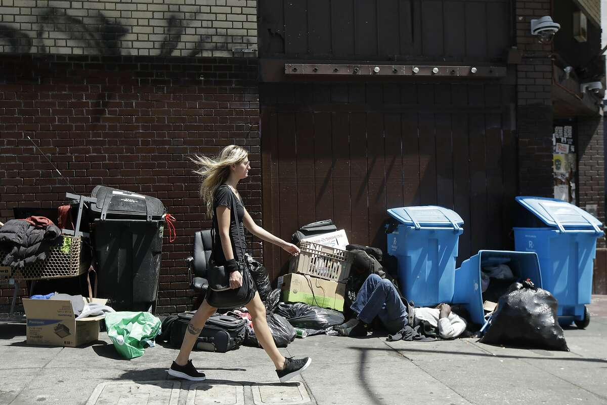 A woman walks past a homeless man sleeping in front of recycling bins and garbage on a street corner in San Francisco, Wednesday, Aug. 21, 2019. (AP Photo/Jeff Chiu)
